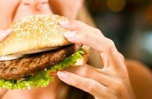 Vrouw met emotionele honger eet een hamburger