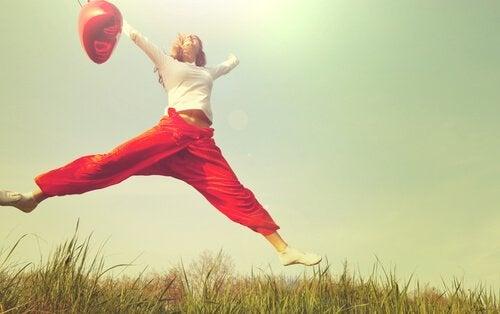 Vrouw die een gat in de lucht springt vanwege haar positieve emoties