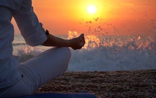 Mediteren op het strand bij zonsondergang dankzij de kennis uit boeken over meditatie