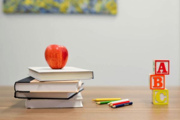 Stapel boeken met een appel erop, om leren voor kinderen met leerproblemen leuker te maken