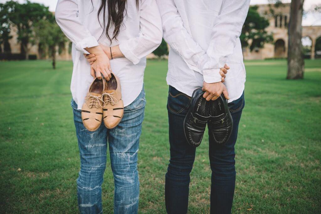 Meisje en jongen met hun schoenen achter hun rug