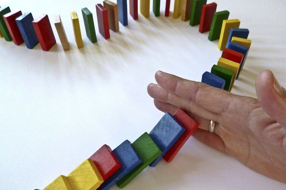 Hand die een paar domino's tegenhoudt, als voorbeeld van sociale macht