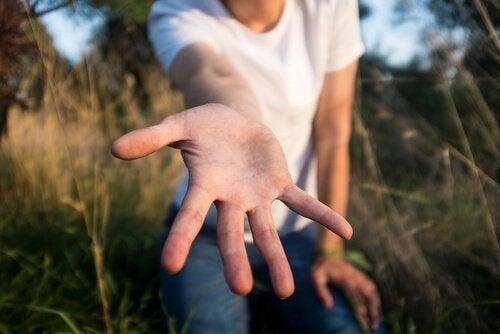 Man die zijn hand naar iemand uitreikt, als voorbeeld van filantropie