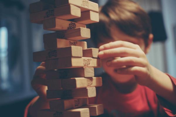 Kind dat in zijn eentje zit te spelen, want mensen hebben vaak een negatief beeld van kinderen met leerproblemen