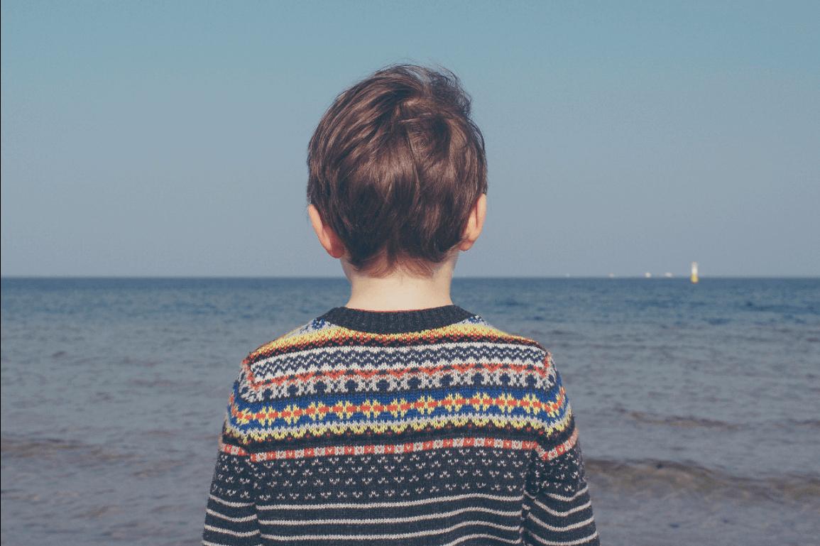 Jongen die uitkijkt over zee en nadankt over zijn morele oordelen
