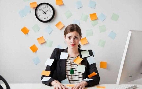 Meisje dat helemaal overspoeld wordt met taken, waardoor jezelf loskoppelen van je werk nog moeilijker wordt