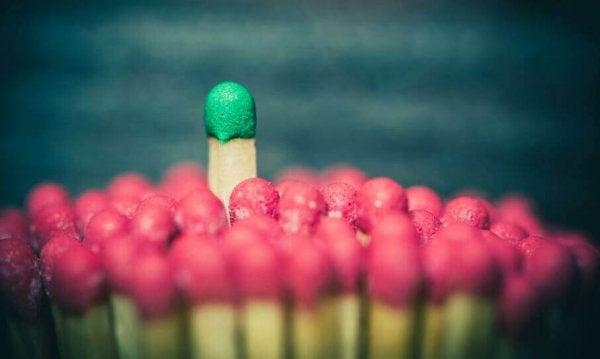 Een groene lucifer die boven allemaal rode lucifers uitsteekt, want dat is wat een leider doet