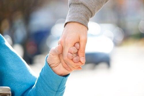 Man houdt de hand vast van een bejaarde vrouw