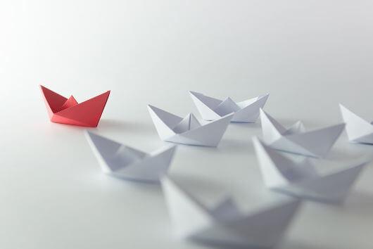 Een rood bootje dat andere witte bootjes leidt, want dat is wat een leider doet