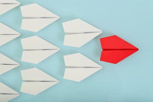 Een rood vliegtuigje dat andere witte vliegtuigjes leidt, want dat is wat een leider doet