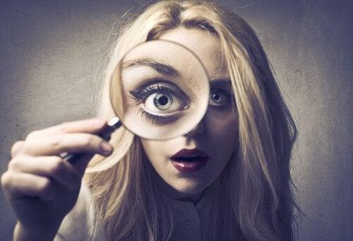 Meisje dat zichzelf bestudeert met een vergrootglas omdat ze te zelfkritisch is