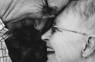Ouder stel kijkt elkaar in de ogen: actief ouder worden