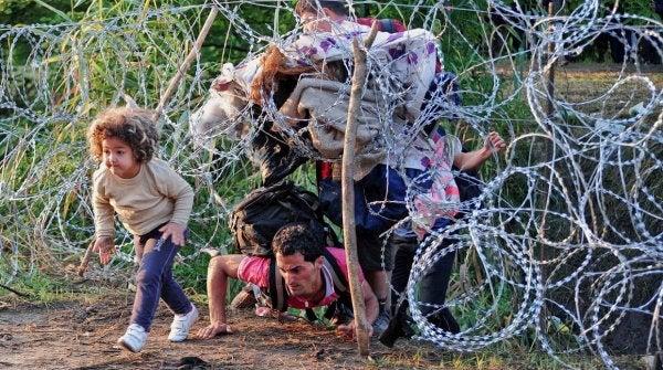 Vluchtelingen die onder een hek van prikkeldraad door kruipen