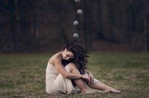 Vrouw zit in het gras: het effect van stress op je lichaam