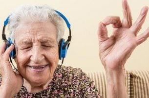 Oudere dame die naar muziek luistert door een koptelefoon