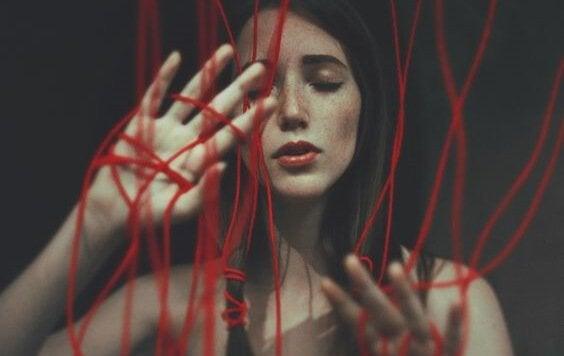 Een meisje dat vaszit in rode draden