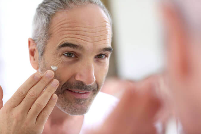 Een man die oogcrème aanbrengt