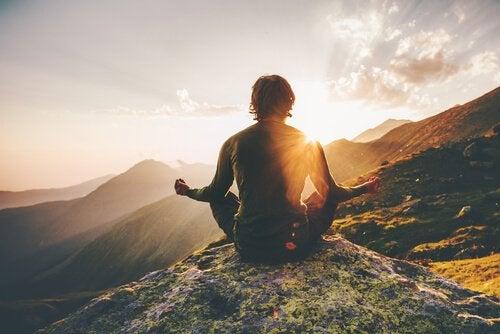 Een man die mediteert op een berg