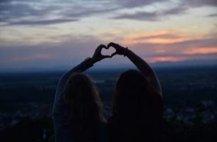 Twee vriendinnen die een hartje maken met hun handen