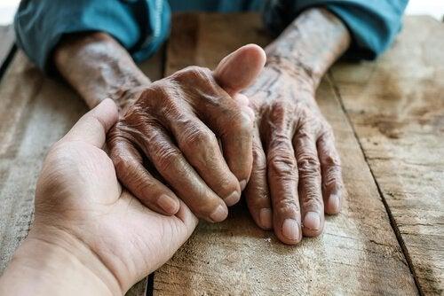 Verzorger houdt handen vast van oudere man