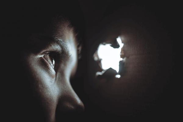 Jongen die door een gaatje in een doos kijkt en last heeft van scheidingsangst