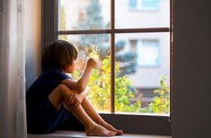 Jongen die uit het raam kijkt en last heeft van scheidingsangst