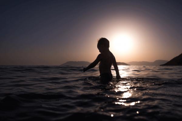 Jongetje dat in de zee loopt en geen last heeft van scheidingsangst