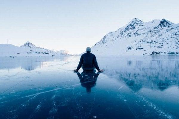 Een man zit op het ijs
