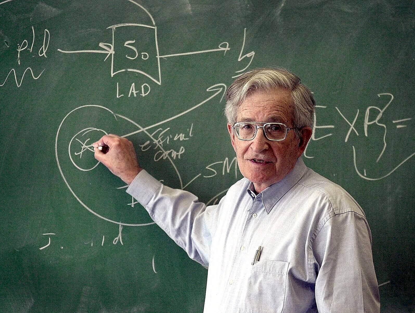 Noam Chomsky die op een bord schrijft