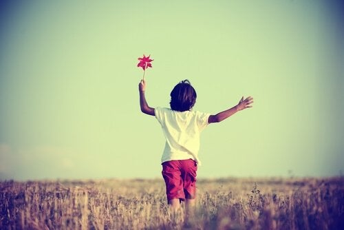 Jongetje dat vrij door een groot veld rent omdat zijn moeder niet een van de overbeschermende supermoeders was