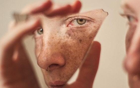 Vrouw kijkt naar zichzelf in gebroken spiegel