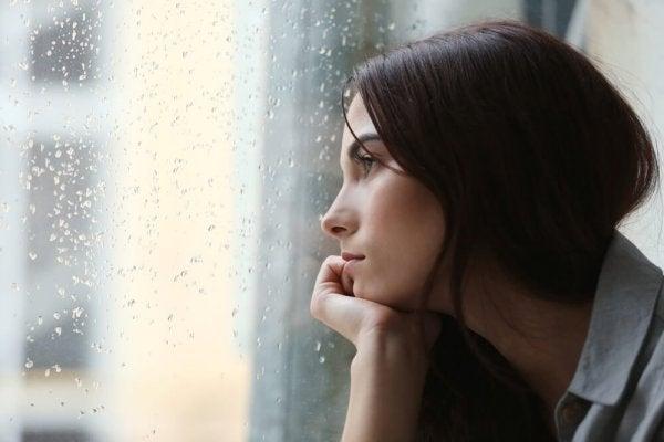 Verdrietige vrouw staart uit het raam