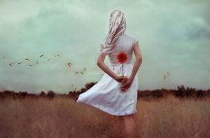 Vrouw met bloem achter haar rug maakt rouwperiode door