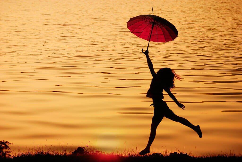 Vrouw die met een paraplu langs het water loopt en zich laat leiden door haar intrinsieke motivatie