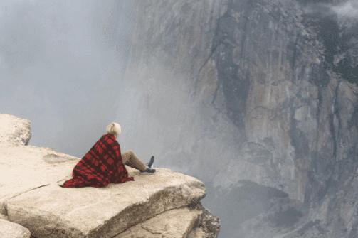 Vrouw die aan de rand van een afgrond zit om over haar fobie heen te komen