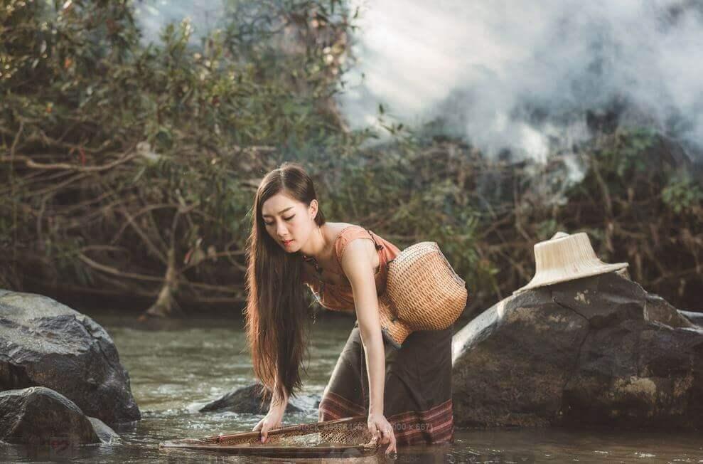 Vrouw die water haalt op een dag met donkere wolken