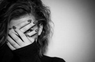 Een vrouw die zich achter haar handen verbergt