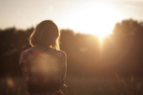 Verdrietige vrouw die naar de zonsondergang kijkt