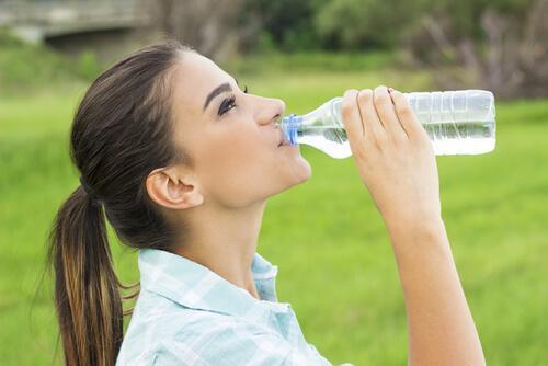 Vrouw die uit een flesje water drinkt