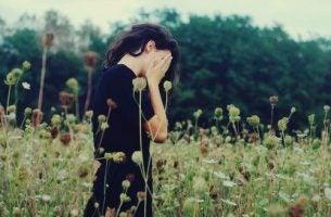Vrouw die staat te huilen in een veld en haar apathie overwinnen moet