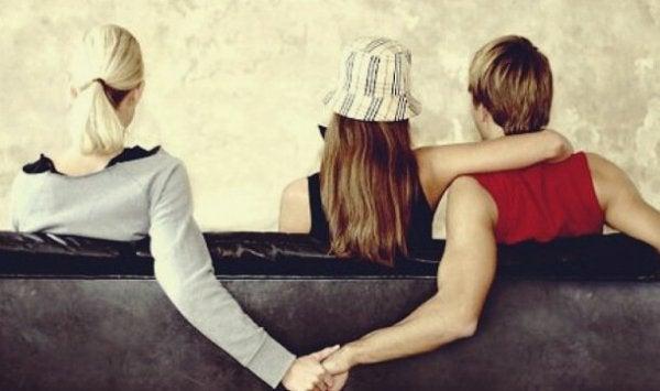 Twee mensen die stiekem elkaars hand vasthouden omdat ze verslaafd zijn aan verboden liefde