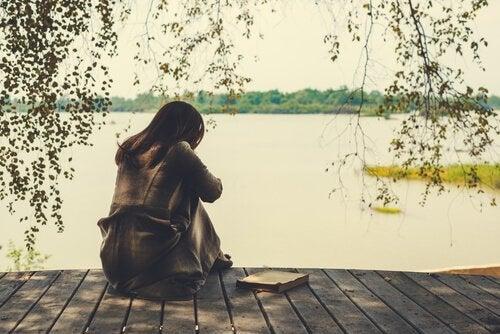 Vrouw die op een steiger aan een meer zit en haar gebroken hart vermijden wil