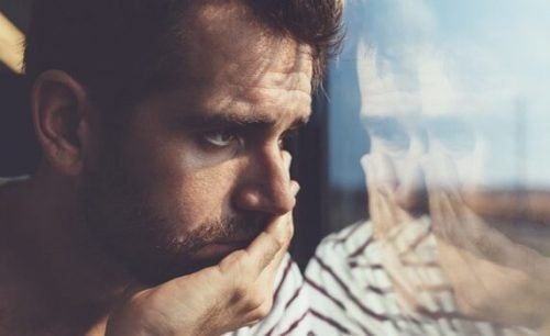 Man die droevig uit een raam kijken en het liefst zijn gebroken hart vermijden wil