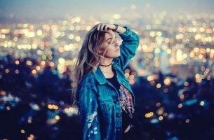 Meisje dat alleen over een grote stad uitkijkt, maar volgens de savanne gelukstheorie hoeft ze niet ongelukkig te zijn