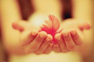 Vrouw die een ander een veertje schenkt, vanwege het belang van vriendelijkheid