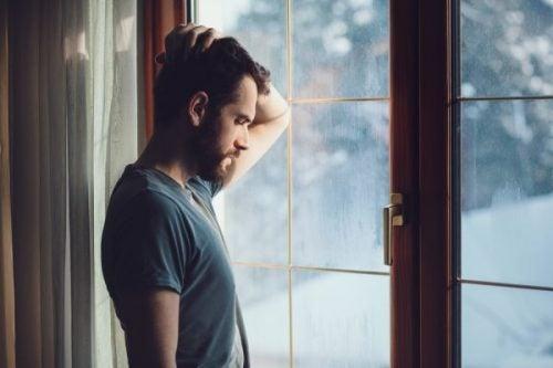 Trieste man bij een raam