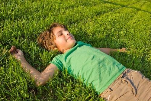 Een van die onafhankelijke kinderen die ligt te genieten in het gras