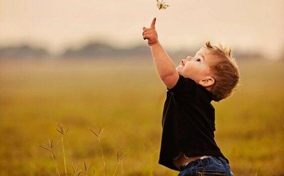 En van die onafhankelijke kinderen die met een vlinder speelt