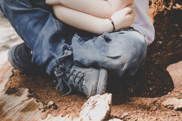 Jongetje dat met zijn benen over elkaar zit, als voorbeeld van emotionele problemen bij kinderen