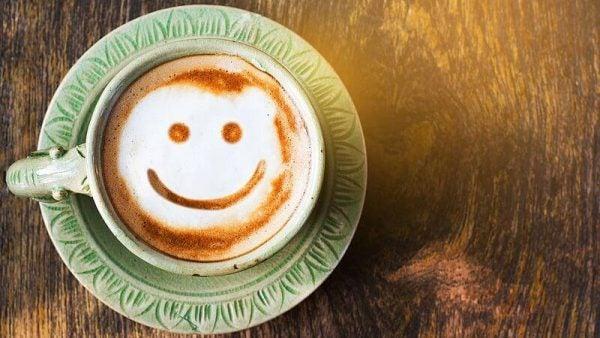 Je lach getekend in het schuim van een kopje koffie